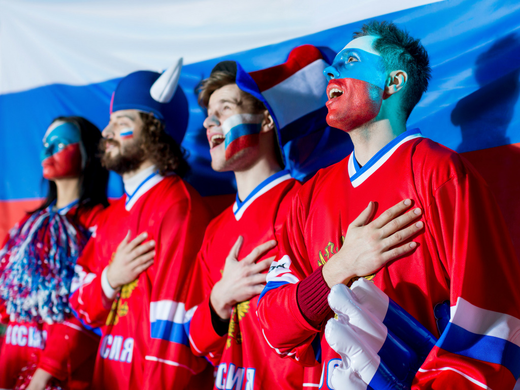 Sports fans dressed up in team colors and make-up - marketing tribes