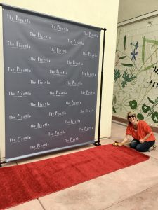 Margot Black taping down red carpet